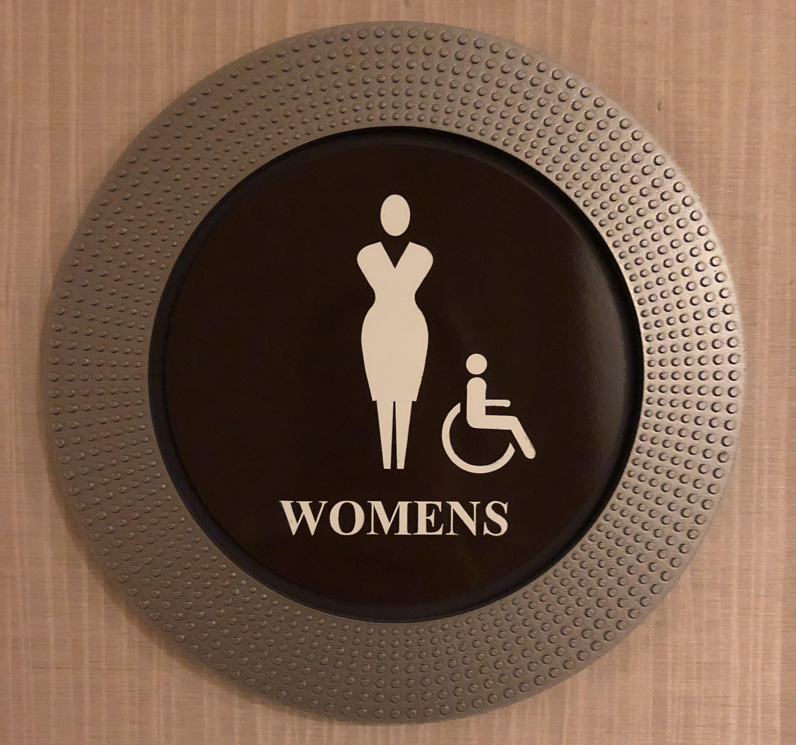 """棕色圆板,头部和面部无特征,没有头发,穿着裙子的曲线身材,""""女人""""和坐在轮椅上的人"""