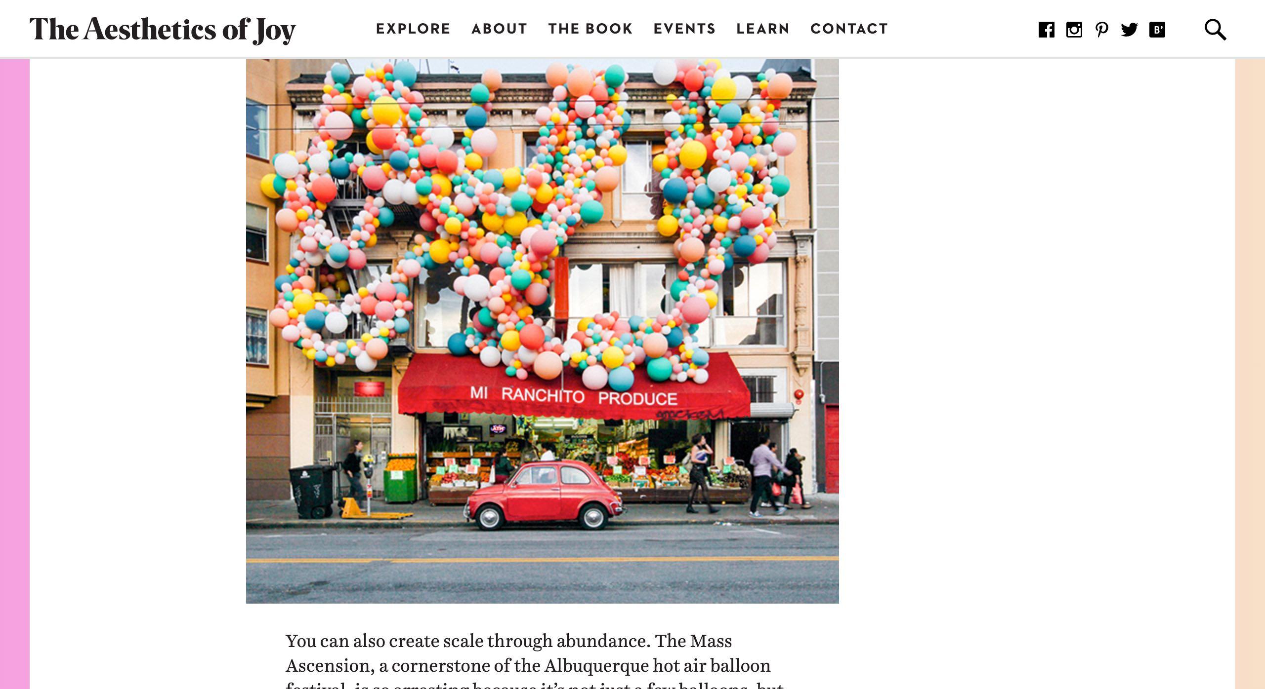 Captura de pantalla del sitio de escritorio de AestheticsOfJoy.com: fotografía colorida de una escultura de globo del tamaño de un edificio