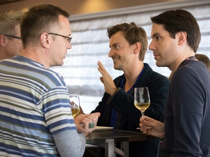 Four men chatting and drinking wine